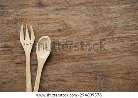 Wooden spoon and fork on wood background