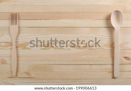 Wooden spoon and fork on wooden boards on unpainted
