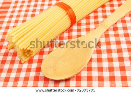 Wooden spoon and macaroni on red checked tablecloth