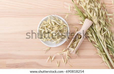 Wooden spoon and Porcelain bowl with dried oat / dried oat tea / Avena