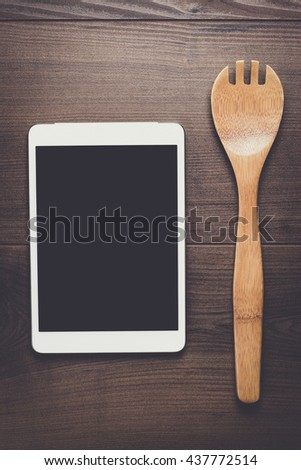 wooden spoon and tablet computer on the brown table - stock photo