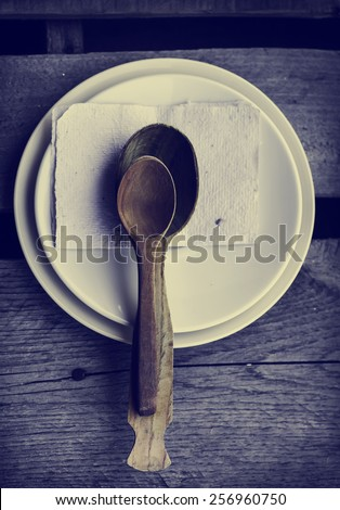 Wooden spoon and white ceramic plates on old wooden table background, Table serving - stock photo