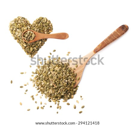 Wooden spoon covered with pumpkin seeds next to the heart shape, composition isolated over the white background - stock photo