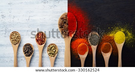 Wooden spoon filled with spices, herbs, powders and ground spices - stock photo