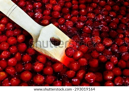 Wooden spoon for stirring when cooking cherry jam - stock photo