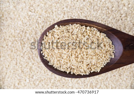 Wooden spoon full of bulgur wheat.