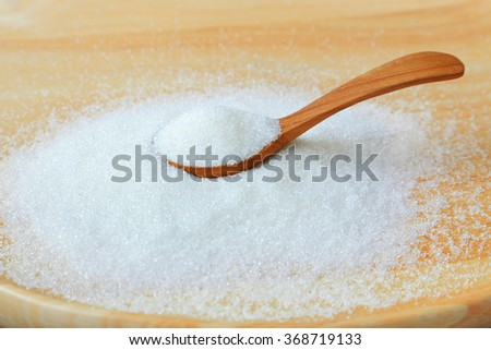 Wooden spoon in a pile of white sugar