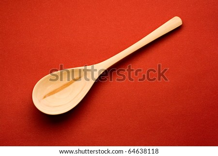 Wooden spoon isolated on red background - stock photo