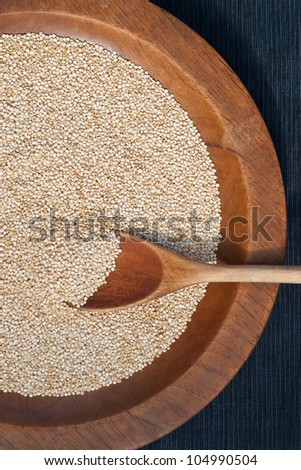 Wooden spoon of quinoa grains in a wooden plate - stock photo