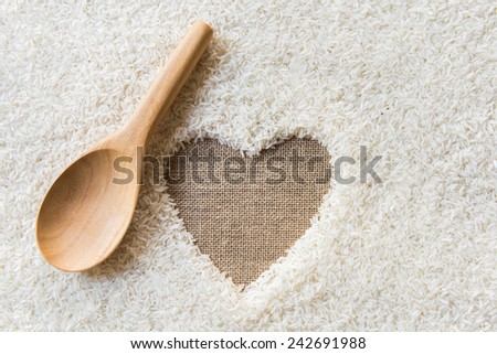 wooden Spoon on rice background Space in the middle of a heart. sackcloth is background - stock photo