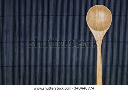 wooden spoon on the black bamboo mat background - stock photo