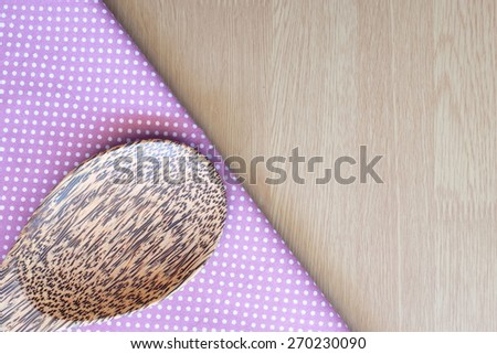 wooden spoon on wooden and dot cloth background