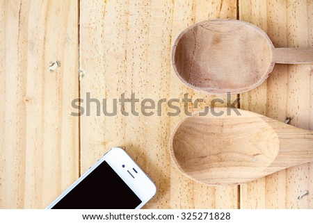 Wooden Spoon on wooden table with mobile phone - stock photo