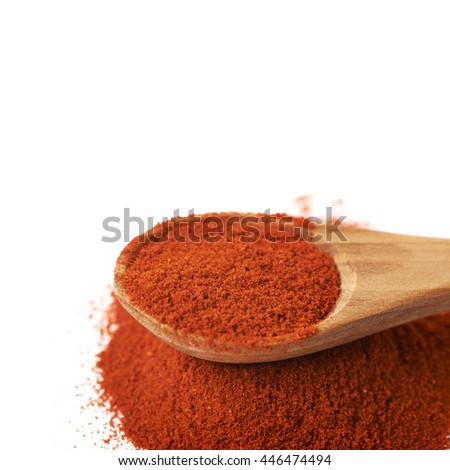 Wooden spoon over the pile of paprika isolated over the white background, close-up crop fragment