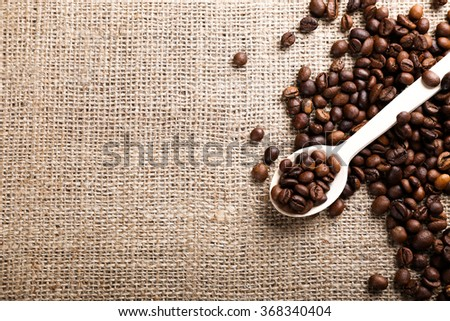 Wooden spoon with coffee beans on burlap background - stock photo