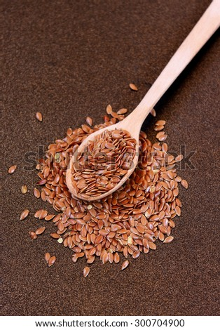 Wooden spoon with flax seeds placed on a metal background, selective focus - stock photo