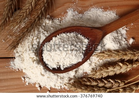 Wooden spoon with flour and wheat ears - stock photo