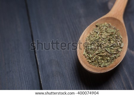 Wooden spoon with green spice on a dark wooden surface