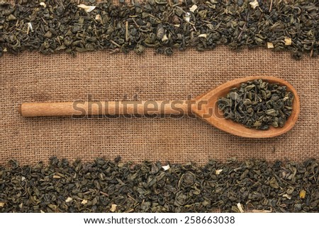 Wooden spoon with  green tea  lies on  sackcloth,as background - stock photo