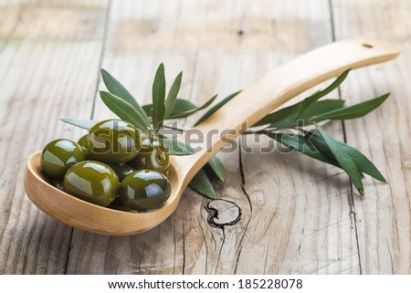 Wooden spoon with olives and oil on the kitchen table - stock photo