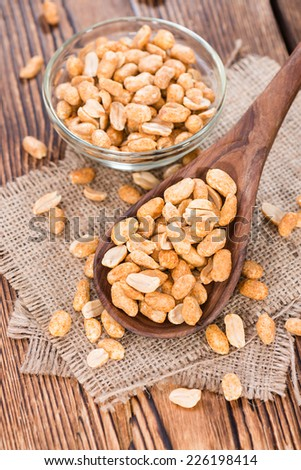 Wooden spoon with Peanuts (roasted and salted) as close-up shot - stock photo