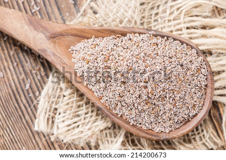 Wooden Spoon with Psyllium Seeds on dark background