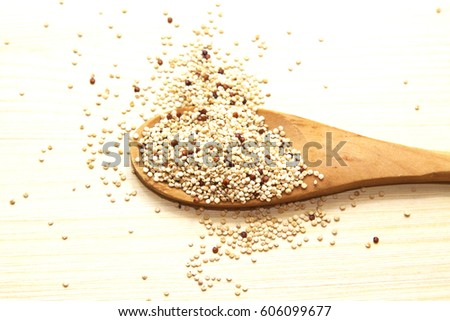 Wooden spoon with quinoa on wooden table