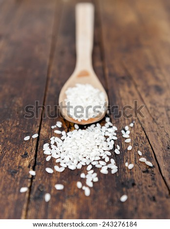 wooden spoon with rice beans on rustic fond - stock photo