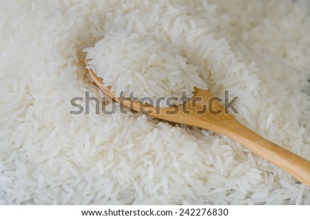 Wooden spoon with rice lying against the background rice - stock photo
