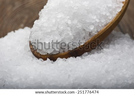wooden spoon with Sea salt poured on wood background  - stock photo
