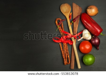 Wooden spoons and vegetables on a black table. Food preparation. Decoration advertising the restaurant.