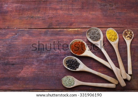 Wooden spoons full of aromatic herbs and spices on a rustic wooden cutting board - stock photo