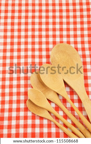 Wooden spoons on red checked tablecloth