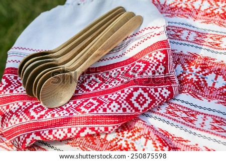 Wooden spoons on table cloth embroidered with red and white folk ornament - stock photo