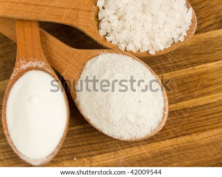Wooden spoons with different kinds of salt. Shallow dof. - stock photo