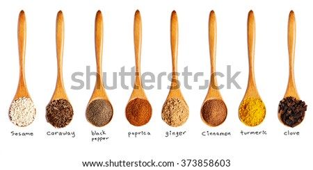 wooden spoons with different spices isolated on white background