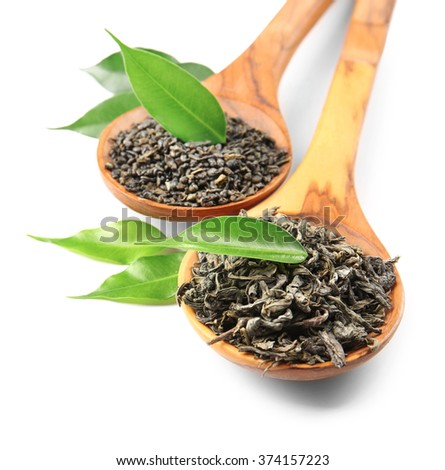 Wooden spoons with dry tea and green leaves, isolated on white