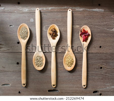 Wooden spoons with spice on old wooden table - stock photo