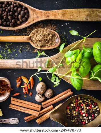 wooden spoons with spices and herbs on textured black background - stock photo