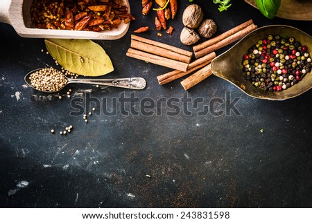wooden spoons with spices and herbs on textured black table - stock photo