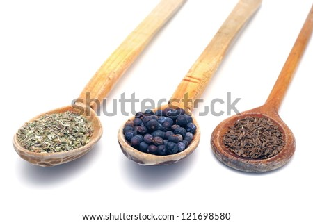 wooden spoons with spices isolated over white background