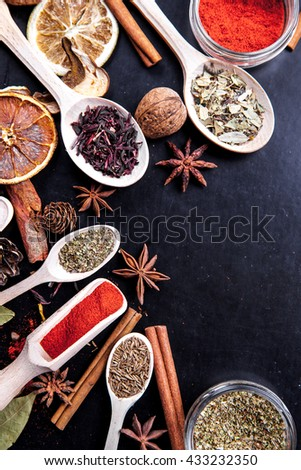 wooden spoons with spices on black background