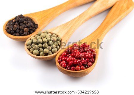 Wooden spoons with various pepper spice on white background