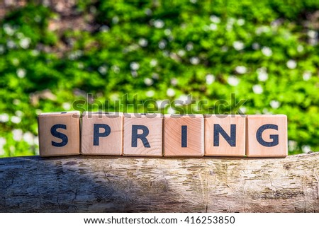 Wooden spring sign in a green forest on a log - stock photo