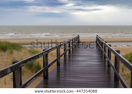 Wooden staircase leading into stormy sky and sea at De Haan, Belgium