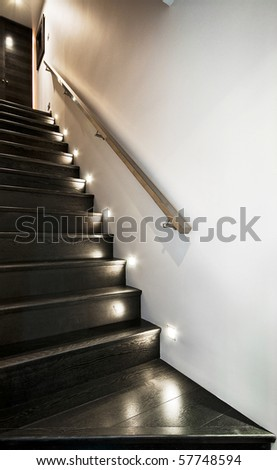 wooden staircase with spotlights and metallic rail - stock photo