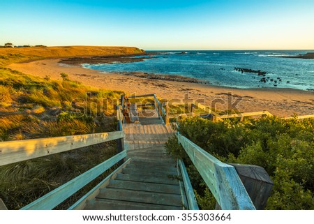 Wooden stairs go down to the beach of Kitty Miller Bay at sunset, in Phillip Island, Victoria, Australia. - stock photo