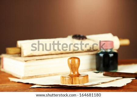 Wooden stamp, books and old papers on wooden table
