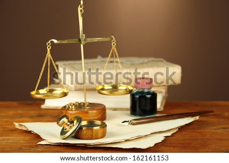 Wooden stamp, scales of justice and old papers on wooden table