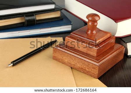 Wooden stamp with notepads  and books on table  - stock photo